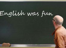 Lehrer vor Tafel, auf der 'English was fun' steht