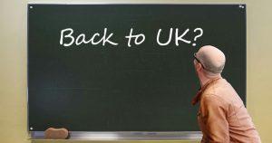 Lehrer vor Tafel, auf der die Frage 'Back to UK?' steht