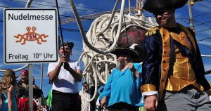 Pastafari mit Piratenkostümen und Hinweistafel auf Nudelmesse am Freitag