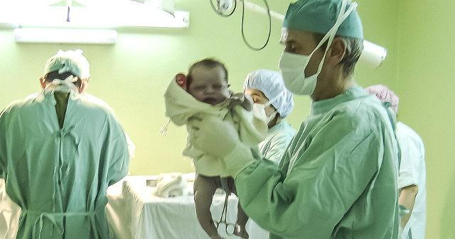 Neugeborenes Baby in den Händen eines Spitalsarztes