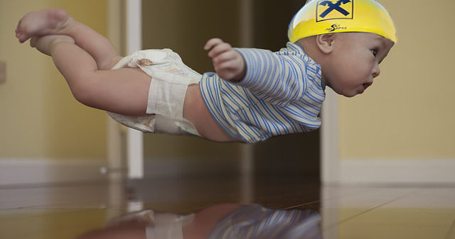 Baby mit Raiffeisen-Helm, das in der Luft schweb