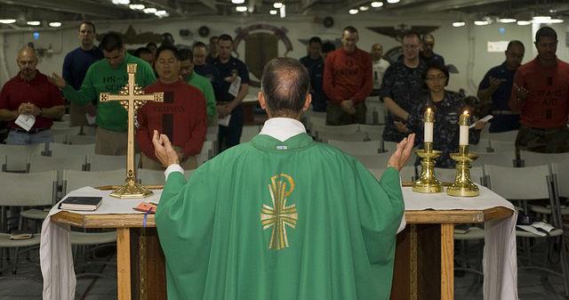 Priester feiert Messe vor Gläubigen